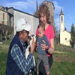 Els padrins i el Jan el petit de la família tocant el corderet - Qui som? Turisme Rural casa l'hereu
